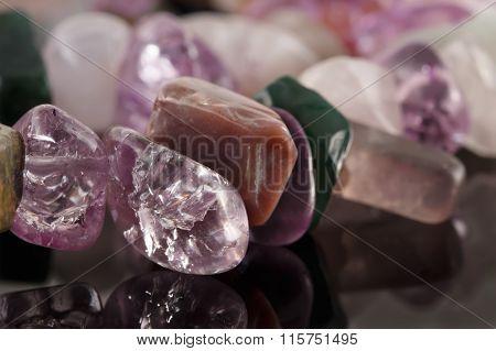 Closeup Crystals Of Amethyst, Fluorite, Jasper And Rose Quartz On Black Table. Selective Focus