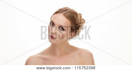 Closeup beauty portrait of young curious blonde woman with bare shoulders looking into camera on whi