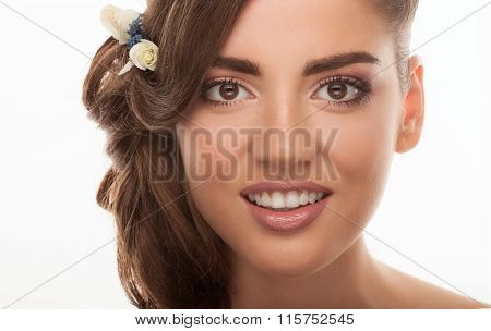 Closeup portrait of young adorable brunette woman showing low bun hairstyle with flower headpiece on