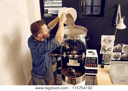 Man pouring raw coffee beans into a modern machine
