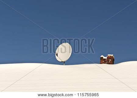 Satellite Antenna And Chimney On Snowy Roof.