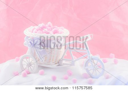 Tricycle souvenir on a pink background with fluffy.
