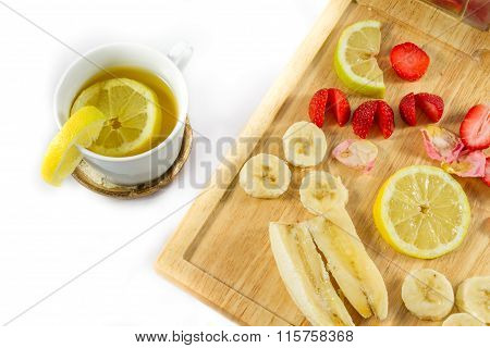 Lemon Tea And Sliced Lemon, Strawberries And Banana On Wooden Board Close-up