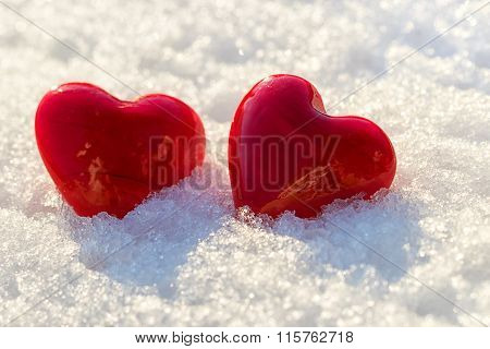 Two red hearts on ice wet snow selective focus