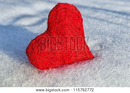 Red heart on ice wet snow selective focus, outdoors image