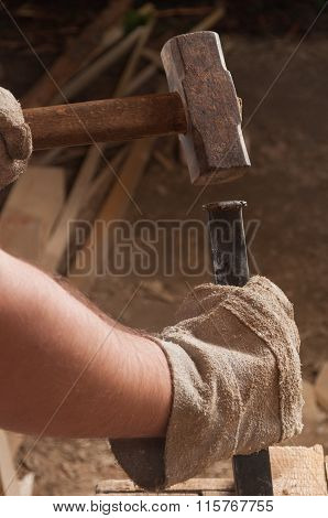 Worker Using A Hammer Hitting A Chisel.