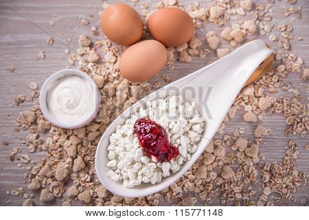 Cottage cheese with jam, eggs on the background of scattered muesli.