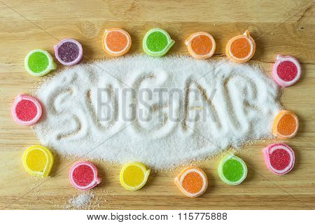 Inscription Sugar Made Into Pile Of White Granulated Sugar On Wooden  Background.