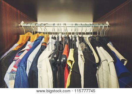 Variety Of Clothes Hanging In Wooden Wardrobe