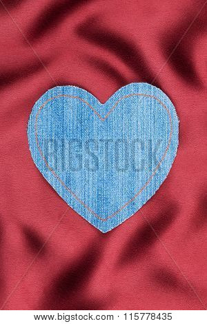 Heart Made Of Denim Fabric With Yellow Stitching On Red Silk
