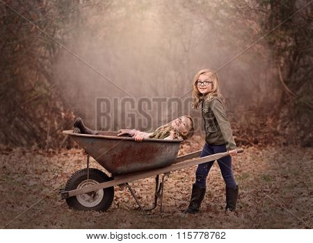 artistic outdoor portrait of two blond girls playing with a wheel barrow in a woods