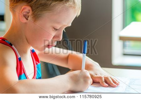 Concentrated Boy Draws A Pen On Paper