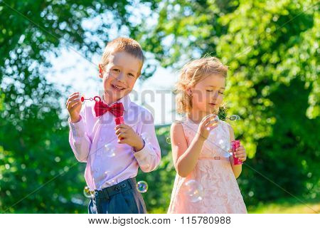Happy Children Play With Soap Bubbles On The Lawn