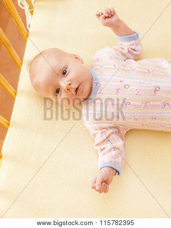 portrait of lying a two month old baby girl in cot