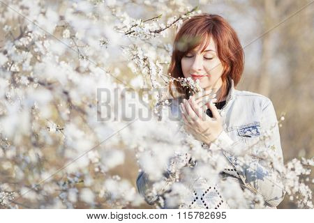 Beautiful smiling woman enjoying of the spring blooming