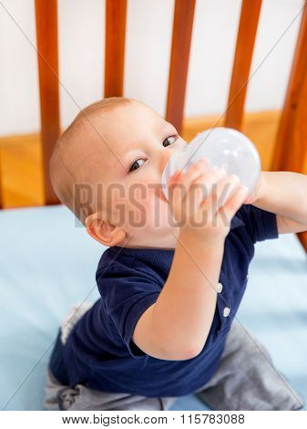 Baby boy smiling in crib holding a bottle