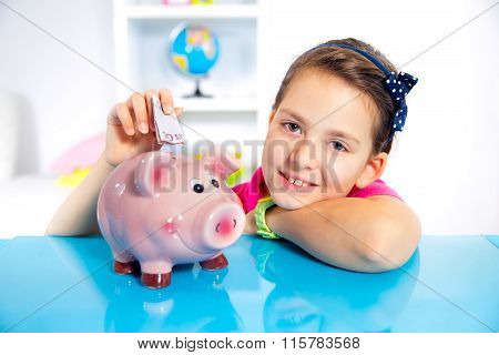 Child with piggy bank.The girl puts money in piggy bank