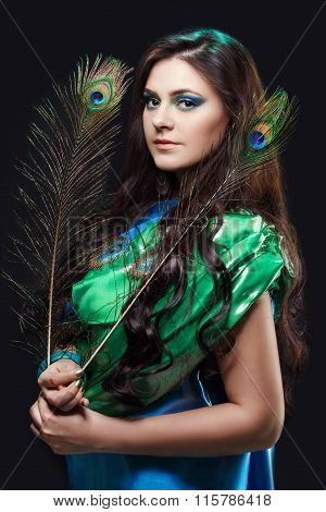 Close up beauty portrait of beautiful girl with peacock feather. Creative makeup peafowl feathers. A