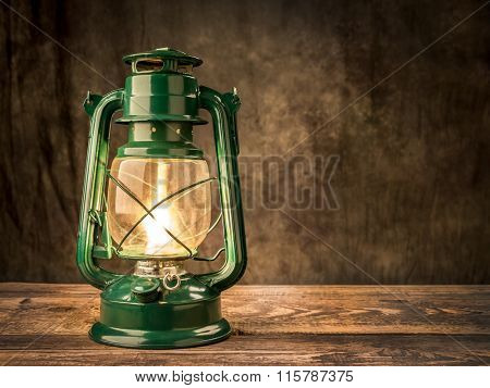 Vintage oil lamp lit on wooden table over dark background