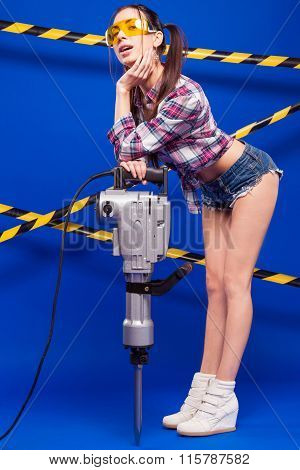 Sexy Brunette In Shorts And Goggles On A Blue Background With A Jackhammer
