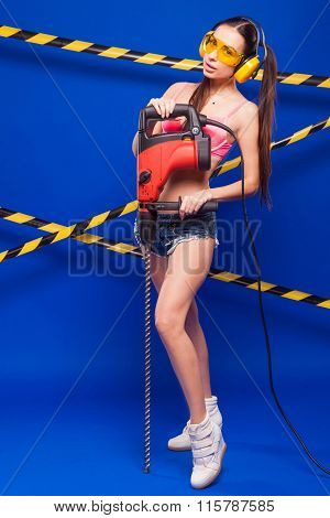 Sexy Brunette Woman In Sunglasses And Headphones Building With Construction Tool Drill Hammer On A B