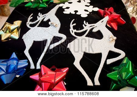 white reindeer artwork with colorful bows surrounding