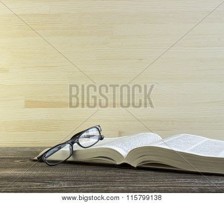 Book And Glasses On A Wooden Table