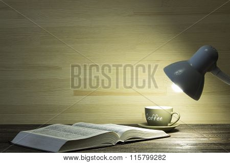 The Book And Cup Of Coffee Are Illuminated By Light From A Lamp