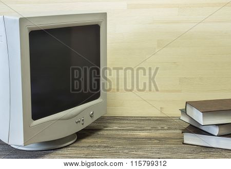 Old Monitor From A Personal Computer And Pile Of Books