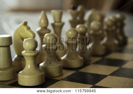 Wooden Chess Board With Figures On The Table.