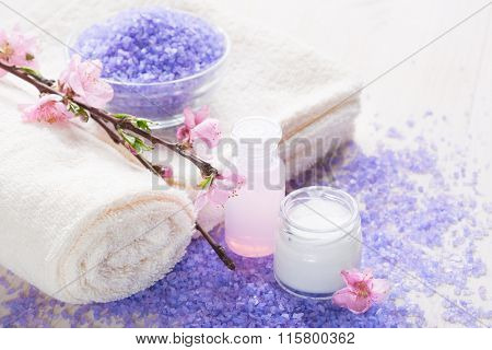 Mineral Bath Salts, towels , moisturizer and  pink spring flowers  .