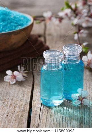 Two small  bottles with shower gel,  mineral bath salts  and spring flowers on the wooden table. Spa concept