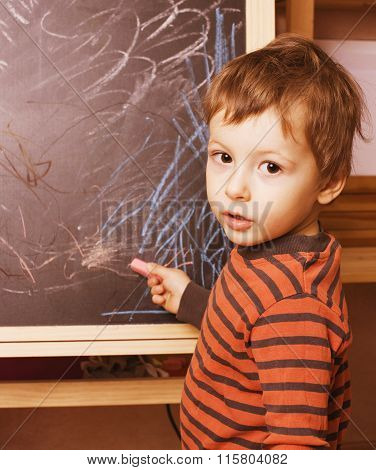 little cute real boy at blackboard in classroom, back to school painting
