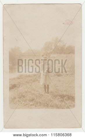 Vintage photo shows a young girl. Photo is over exposed.