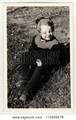Vintage photo shows a small girl sits on grass circa 1941