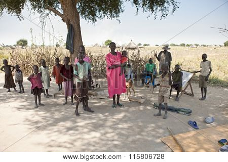 LILIIR, SOUTH SUDAN-DECEMBER 4, 2010: Unidentified large family stands in the shade of a tree in rural South Sudan