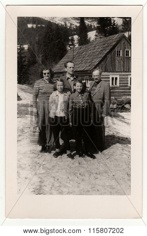 A vintage photo shows group of people In front of a log house in winter, circa 1950s.