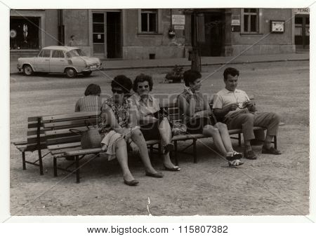 Vintage photo shows people sit on a bench, circa 1950s.