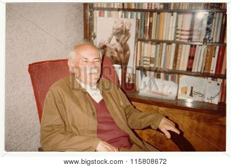 Vintage photo shows man sits on armchair, circa 1980s.