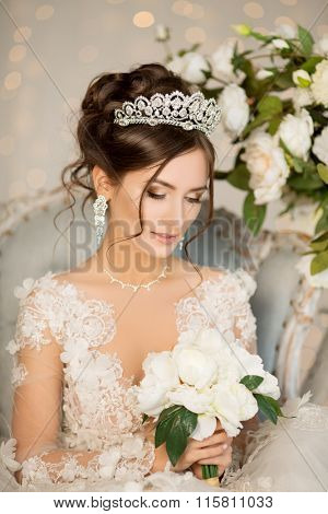 Bride. Wedding. The bride in a short dress with lace in the crown earrings. Wedding bouquet, makeup,