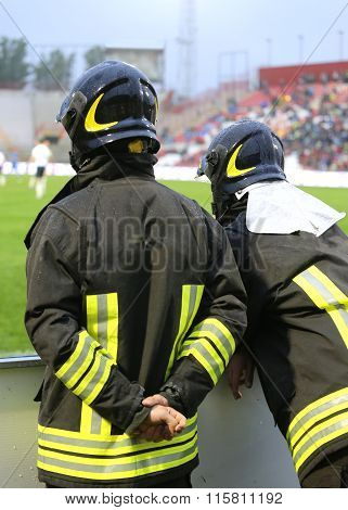 Two Firefighters With Hardhat During The Sports Event