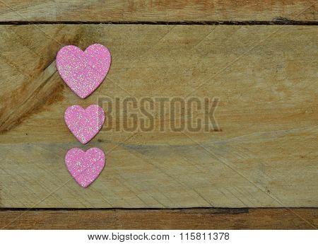 Glittering pink hearts set on pallet wood