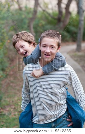 Happy Brothers Riding Piggyback At The Park