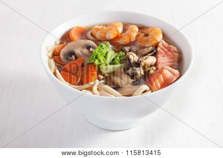 seafood soup shrimp mussels pasta fish mushrooms in a bowl isolated on white background