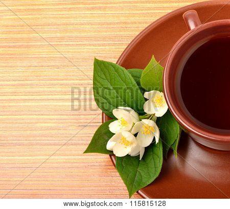 Tea On The Ceramic Cup With Jasmine Flower On The Wood