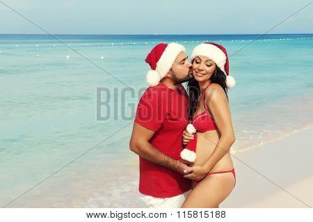 Happy Pregnancy, Pregnant Family. Expectant Parents In Christmas Costumes And Santa Hat On The Sea.