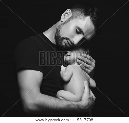 Newborn Baby Sleeping In His Arms Of Father On Dark
