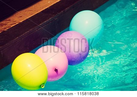 yellow pink blue and purple balloons float in water pool