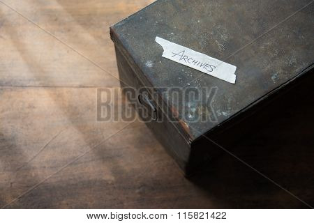 Archives storage box. Very old document storage box on old desk. Focus is on top label. Shallow depth of field. low key.