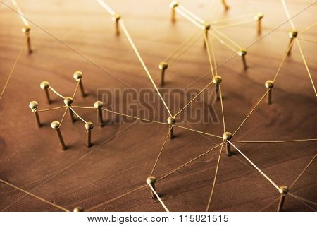 Linking entities. Network, networking, social media, internet communication abstract. A small network connected to a larger network. Web of gold wires on rustic wood.